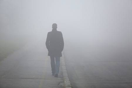 52651500-alone-man-from-back-walking-through-the-fog-on-street